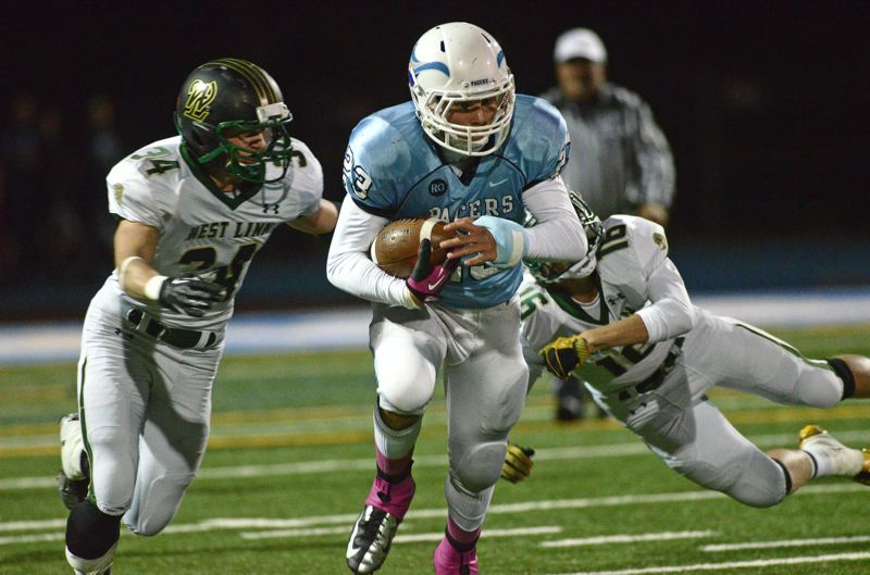 by: VERN UYETAKE - Lakeridge's Alex Alamida tries to shake off a pair of West Linn tacklers during last week's regular season finale against the Lions.