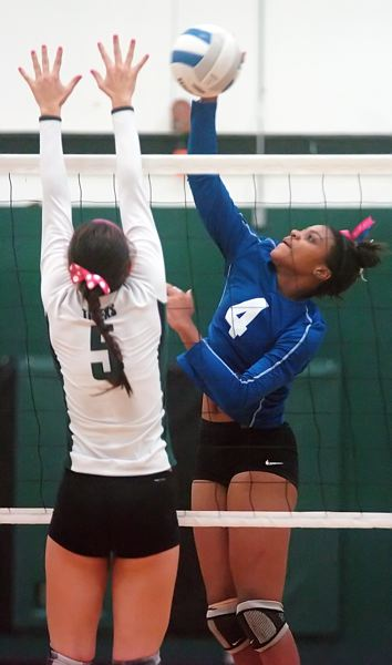 by: PAMPLIN MEDIA GROUP: DAN BROOD - Grant junior Janae Davis goes up for a kill over Tigard senior Lauren Becker in their postseason match.