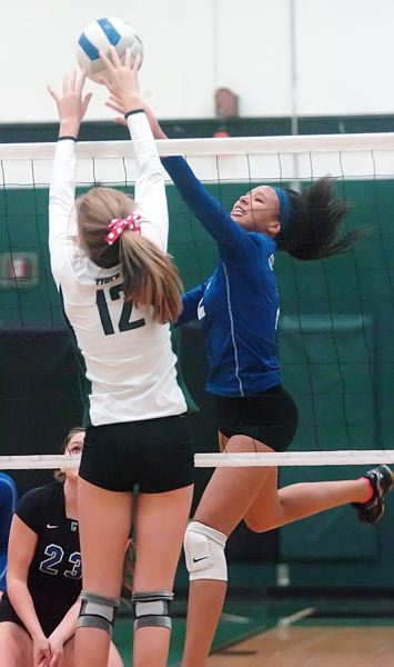 by: PAMPLIN MEDIA GROUP: DAN BROOD - Grant senior Paige Moreland and Tigard sophomore Ashley Holzgang go up for the ball at the net.
