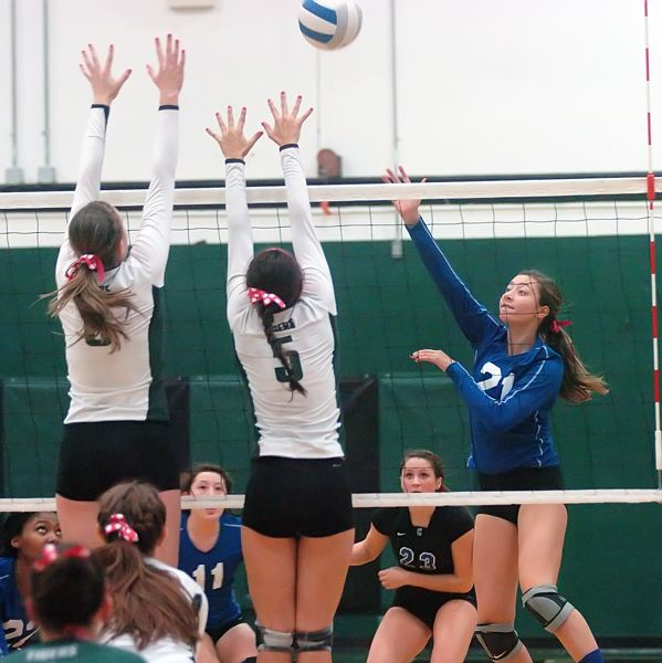 by: PAMPLIN MEDIA GROUP: DAN BROOD - Grant sophomore Maddy Siberger-Franek tries to hit the ball over Tigard's Michelle Simmons and Lauren Becker.
