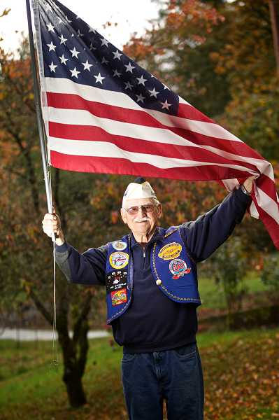 by: TIMES PHOTO: JAIME VALDEZ - Albert 'Monty' Montague, a Pearl Harbor survivor, holds the American flag outside his home in Tualatin.