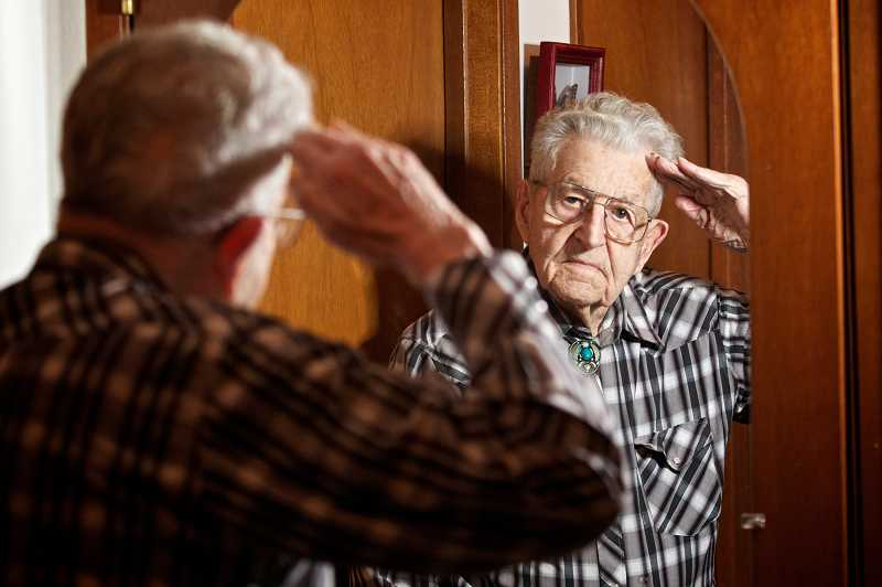 by: TIMES PHOTO: JAIME VALDEZ - Les Jones, a former World War II prisoner of war, salutes in a mirror at his Tualatin home. He plans to attend the Veterans Recognition Breakfast, which will take place Friday, Nov. 9, in Tualatin.