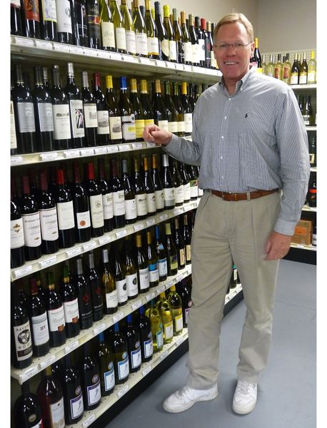 by: DREW DAKESSIAN - Bruce Randall points to his favorite wine: Jordan Cabernet Sauvignon.