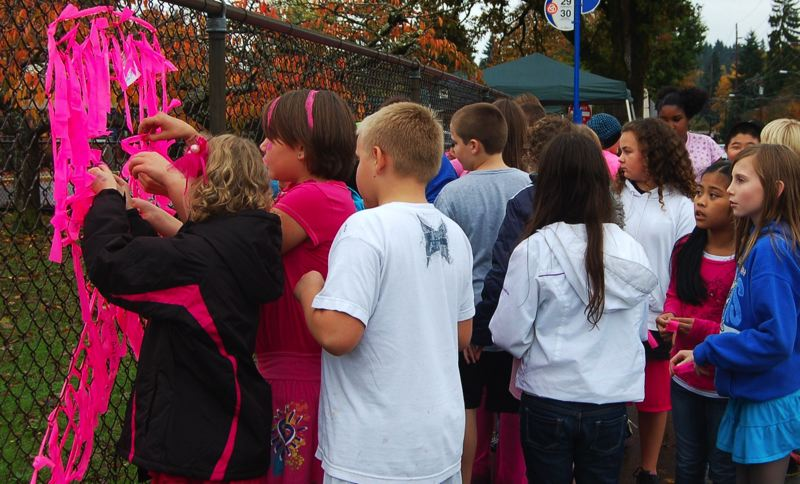 by: SUBMITTED - Fourth-grade teacher Kim Buzan appreciates the support from Bilquist Elementary School students putting up pink ribbons.