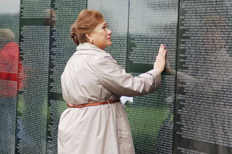 by: SUBMITTED PHOTO - A visitor reflects on the thousands of names at the Traveling Dignity Memorial Vietnam Wall.