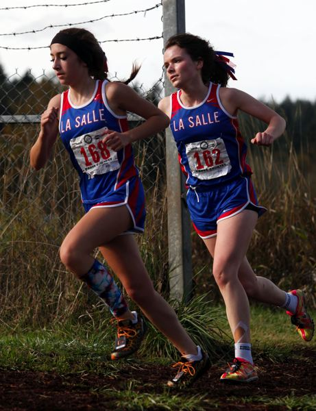 by: JONATHAN HOUSE - La Salle freshman Carly Veasy and senior Kelsey Cathcart take a turn at the two-mile mark at Saturdays Class 4A State High School Cross Country Championships, contested under sunny skies at Lane Community College.