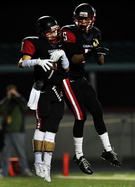 by: JOHN LARIVIERE - Ryan Gilbert (left) and Jacob Iverson (5) celebrate a touchdown in Friday nights 49-28 state play-in win over North Medford.