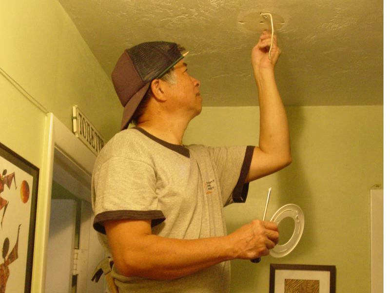 by: PHOTO BY MERRY MACKINNON - Wai Ming Tang, Community Energy Project service technician, installs a new smoke alarm in Phyllis Melson-Fords North Portland house. The nonprofit organization does free weatherization and repair services in the homes of low-income seniors and adults with disabilities.