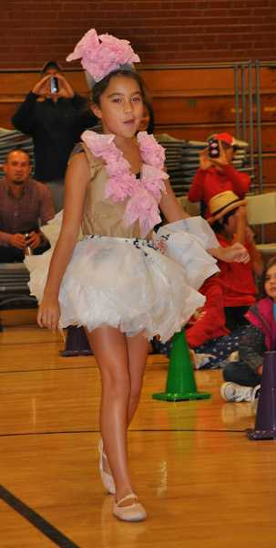 by: MICHAEL QUISLING - Fifth-grader Briana Alexander models her pretty in pink dress made of plastic bags at the Trashion Fashion Show at Bolton Primary School.
