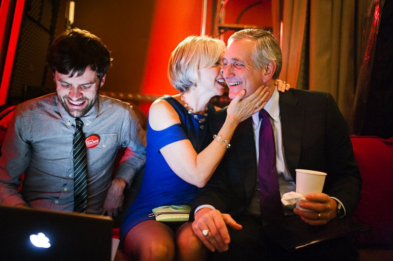 by: TRIBUNE PHOTO: CHRISTOPHER ONSTOTT - Portland Mayor-elect Charlie Hales gets a kiss from his wife Nancy as campaign staffer Brian Rae checks election numbers Tuesday night.