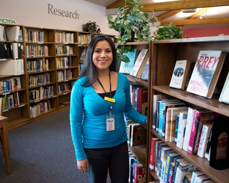 by: NEWS-TIMES PHOTO: CHASE ALLGOOD - Maria Aguilar, Latino outreach coordinator for the Cornelius Library, grew up in town and remembers checking out the same cookbook from the library over and over.