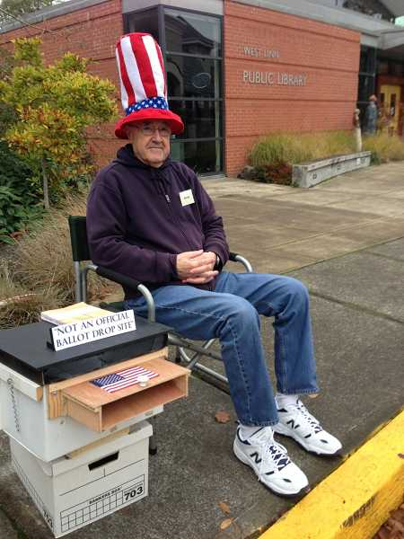 by: LORI HALL - Alan Lewis sits in front of the West Linn Public Library every election day morning collecting ballots for people before the library opens.