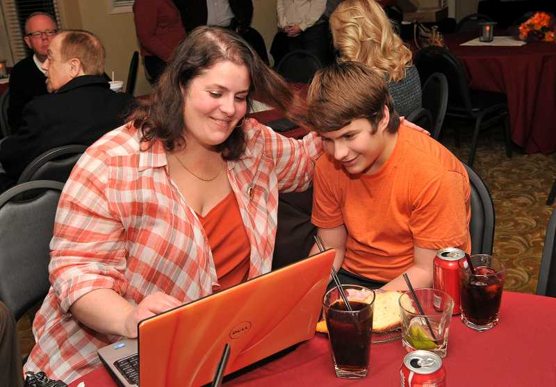 by: VERN UYETAKE - Julie Parrish and her son Max check the election results at a election night gathering at the Century Hotel in Tualatin.