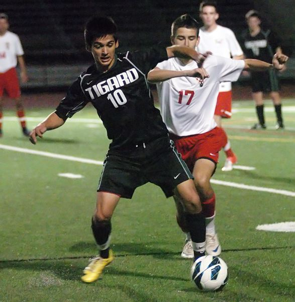 by: DAN BROOD - PLAYOFF BATTLE -- Tigard junior Javier Sanchez-Figueroa (left) keeps Lincoln junior Michael Sheldon away from the ball.