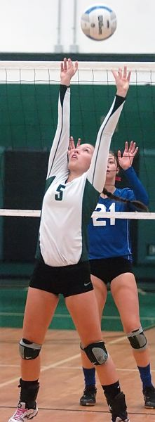by: DAN BROOD - ARMS UP -- Tigard senior Luaren Becker sets the ball during the Tigers' playoff victory.