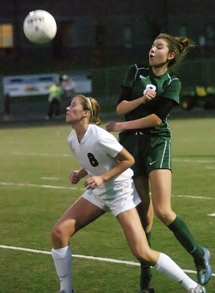 by: DAN BROOD - HIT IT UP -- Sherwood senior Carley Mills (front) heads the ball upward in front of Wilson junior Ellen Berkley during the Lady Bowmen's 1-0 state playoff win.