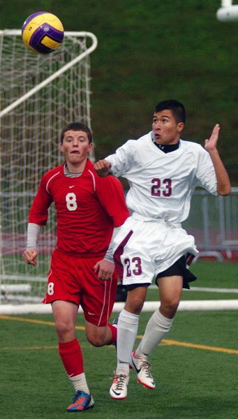 by: DAN BROOD - HEAD GAMES -- Tualatin junior David Bello (23) heads the ball away from Centennial juniopr Austin Feltner.