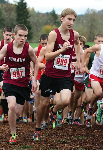 by: JONATHAN HOUSE - LEADING THE PACK -- Matthew Lovos leads a pack of Tualatin runners up hill during Saturday's Class 6A state cross country championships.
