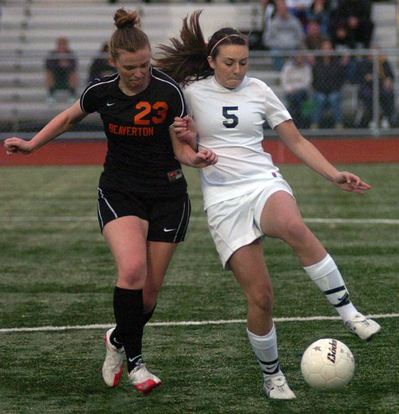 by: DAN BROOD - KEEPING IT -- Tigard sophomore Rachel Simmons (right) keeps the ball away from Beaverton's Kelly Priest in Saturday's playoff match.