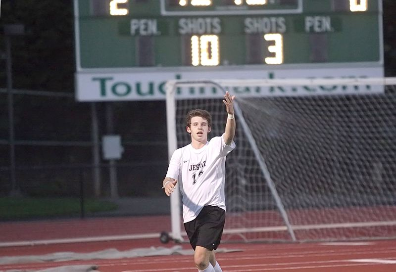 by: MILES VANCE - SCORING MACHINE - Jesuit's Henry Rocker signals the Crusader crowd after scoring one of his three goals during Jesuit's 7-0 home win over David Douglas on Tuesday.