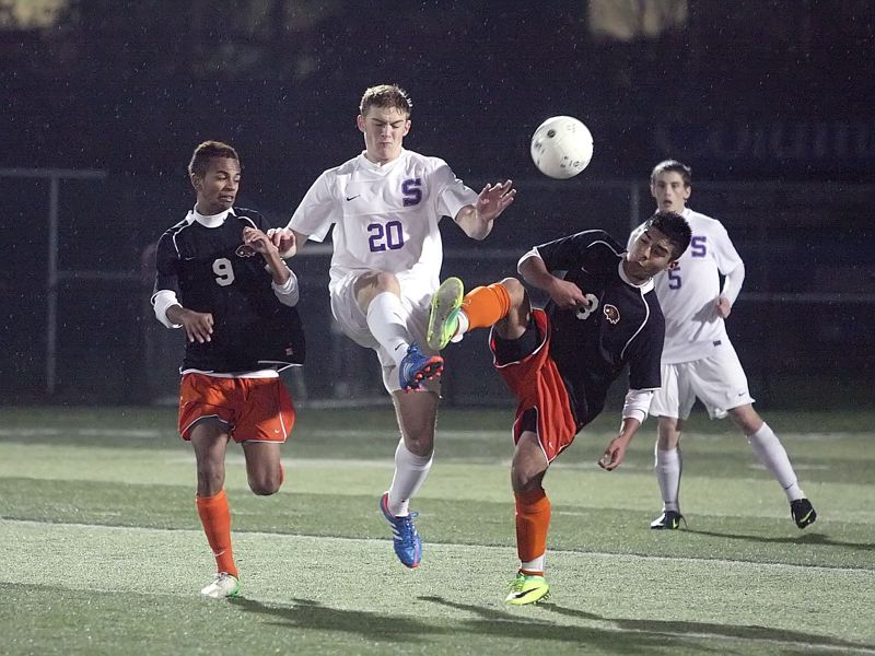 by: MILES VANCE - BATTLE BALL - Sunset's Mason Crow (center) flies between Beaverton's Ian Coleman (left) and Abel Guzman during his team's 2-1 victory over the Beavers in penalty kicks in the second round of the Class 6A state playoffs at Sunset on Tuesday.