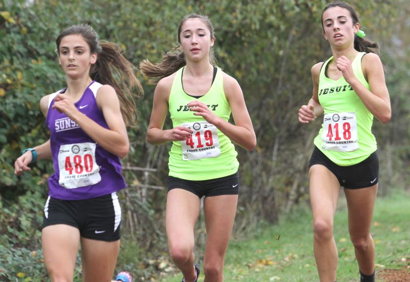 by: JONATHAN HOUSE - METRO THREE - Charlotte Corless of Sunset (left) leads Ellie Kallgren and Dylan Hite of Jesuit during the Class 6A state meet at Lane Community College in Eugene on Saturday.