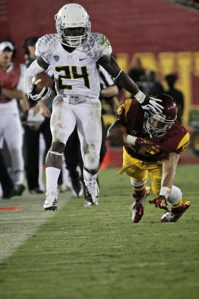 by: TRIBUNE PHOTO: JAIME VALDEZ - Kenjon Barner eludes the USC defense on a jaunt down the sidelines, as the Oregon Ducks beat the Trojans 62-51.