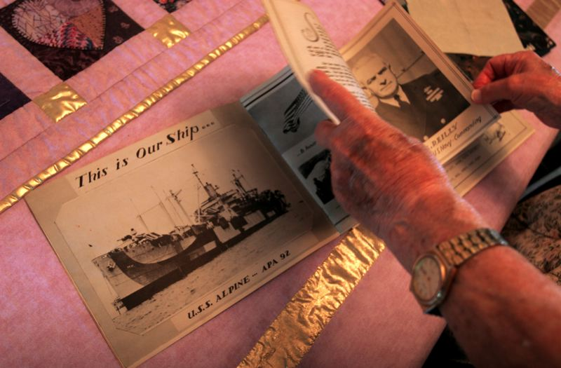 Jim Bean goes through his ship's yearbook from WWII. The vessel he served on is shown on the open page. OUTLOOK PHOTO: JIM CLARK