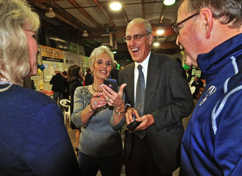 by: VERN UYETAKE - Kent Studebaker and his wife, Kim, check the latest election results Tuesday night at a Lakeview Boulevard warehouse party also attended by council candidates Karen Bowerman, Skip O'Neill and Dan Williams.