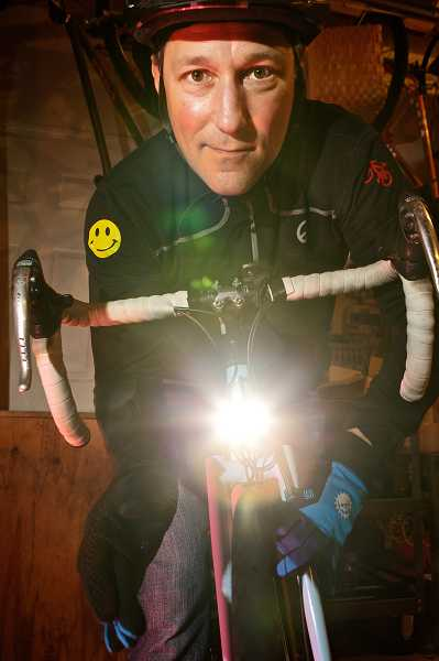 by: JAIME VALDEZ - Brian Engelen shows off his 'DynoLight,' a bicycle light powered by a generator in teh wheel hub.