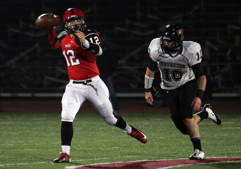 by: JONATHAN HOUSE - Oregon City sophomore quarterback Austin Whitton (12) is pressured by Thurston 210-pound linebacker Kyle Watson (10) in Friday nights 30-28 loss to the Colts.