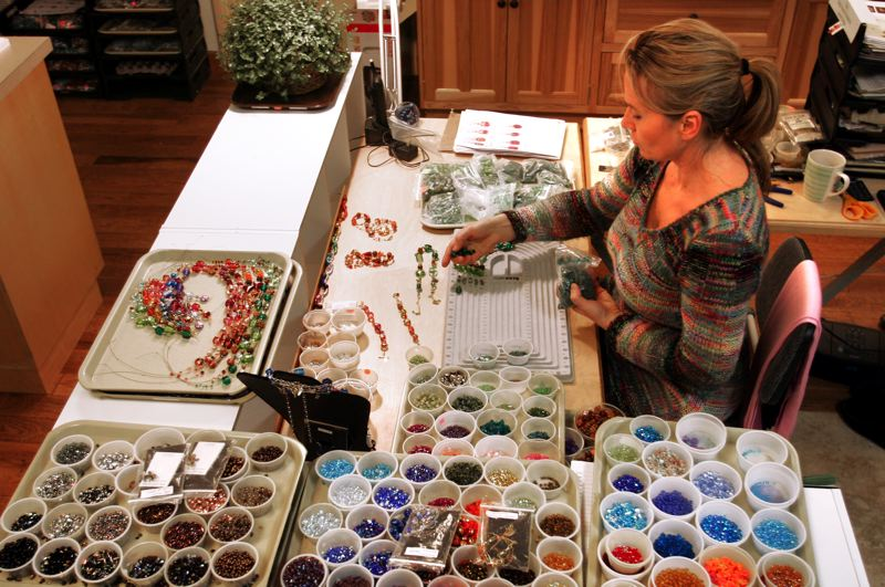 by: OUTLOOK PHOTO: JIM CLARK - Jewelry maker Liya Cot assembles a necklace at Marco Polo Designs in Troutdale.