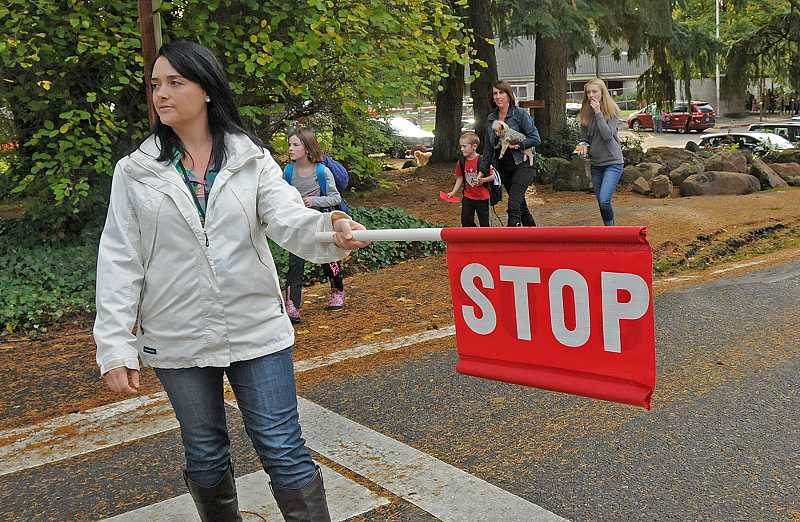 by: REVIEW PHOTO: VERN UYETAKE - Instructional aide Jaine Sutton stops traffic for students coming out of the new River Grove Safe Path.