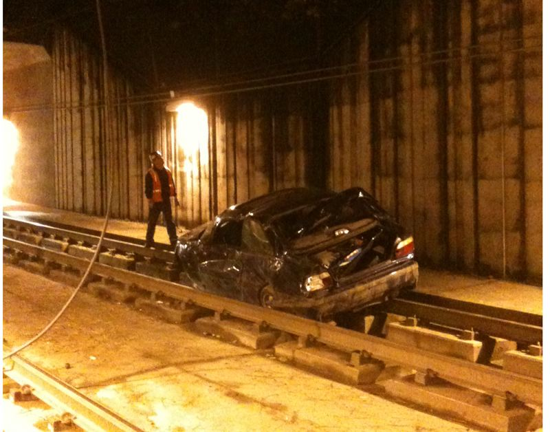 by: BEAVERTON POLICE DEPARTMENT - A worker inspects damage in the tunnel near the Sunset Trasnit Center caused by a Tuesday night car accident.