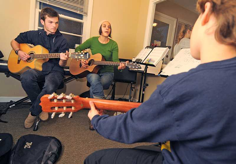 by: VERN UYETAKE - Instructor Monica Metzler and intern Michael Wiest lead a guitar class on Nov. 20.