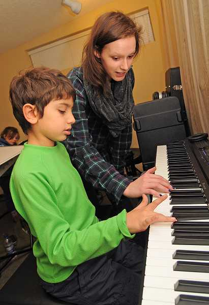 by: VERN UYETAKE - Piano instructor Caroline Doctor helps Alex Aghdaei with his fingering technique at Youth Music Project.
