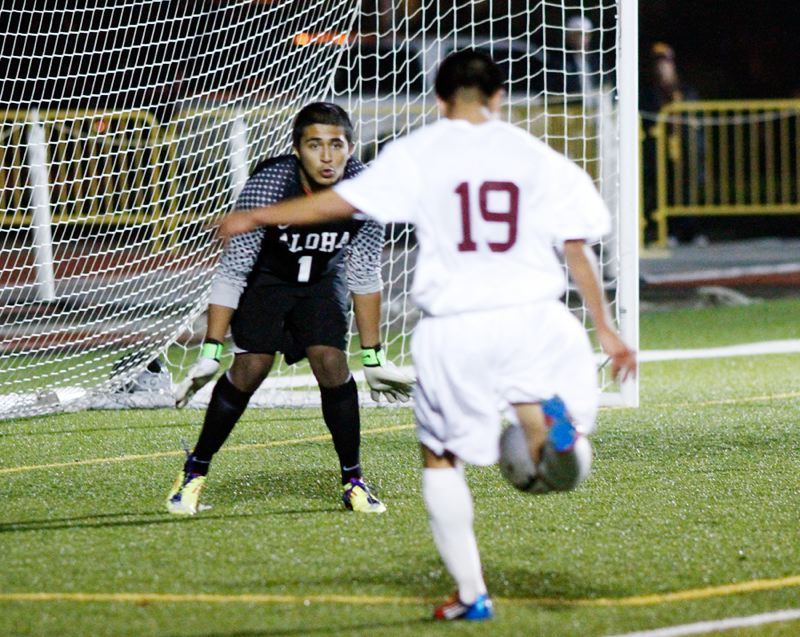 by: CHASE ALLGOOD - Forest Grove's Jairo Aguilar Ortiz prepares to fire a shot on Aloha goalkeeper Jorge Rodriguez during last week's playoff match.