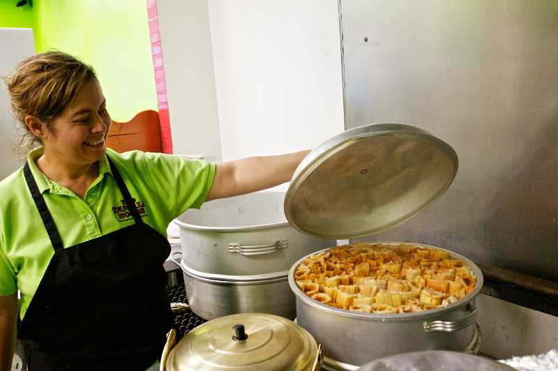 by: JAIME VALDEZ - Magdalena Jump inspects a pot of tamales cooking at The Tamale House. The restaurant is known as one of the few places to get the traditional holiday dish in Washington County.