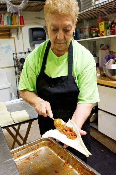 by: JAIME VALDEZ - Josefina Rosas spoons pork into a tamale at The Tamale House in Tigard. The two-year-old restaurant is gearing up for the holiday season where they expect to make about 10,000 tamales.