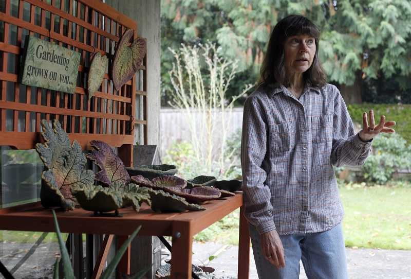 by: JONATHAN HOUSE - Cedar Hills artist Roberta Palmer discusses the process behind her painted, concrete-cast leaves near the workshop in her backyard, the original source of the leaves.