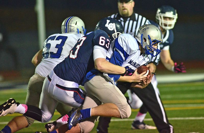 by: VERN UYETAKE - Lake Oswego's Andrew Wrenn makes a tackle during last week's playoff-opening victory. The Laker defense shut out McNary at home.