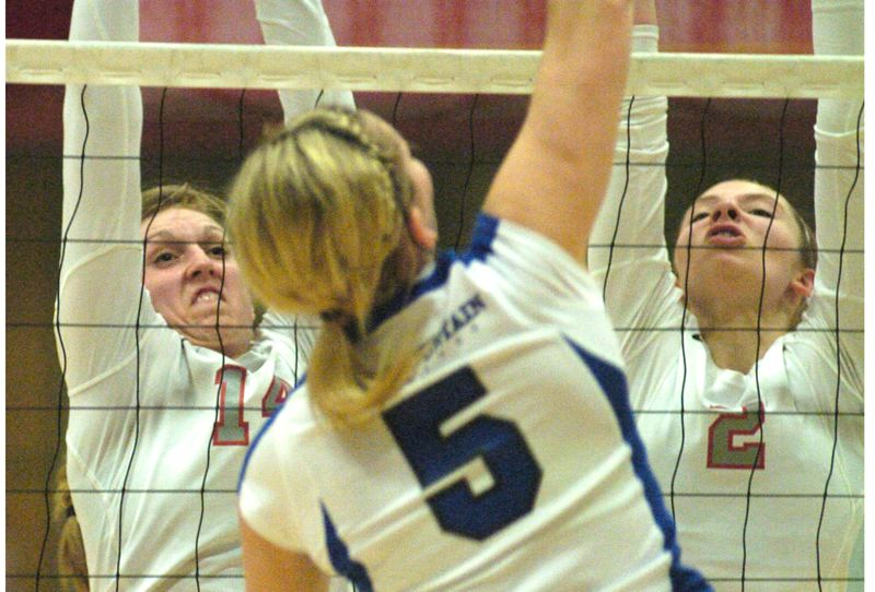 by: THE OUTLOOK: DAVID BALL - Mt. Hoods Maycee Abendschein, left, and Keely Siegel put up a block on Blue Mountains Kendra DeHoog during the Timberwolves five-set victory Friday night.