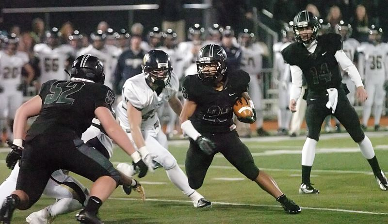 by: DAN BROOD - ZACH ATTACK -- Tigard senior Zach Floyd (23) looks for running room in Friday's state playoff second round game. Floyd rushed for 320 yards and three touchdown in the Tigers' 42-14 win.