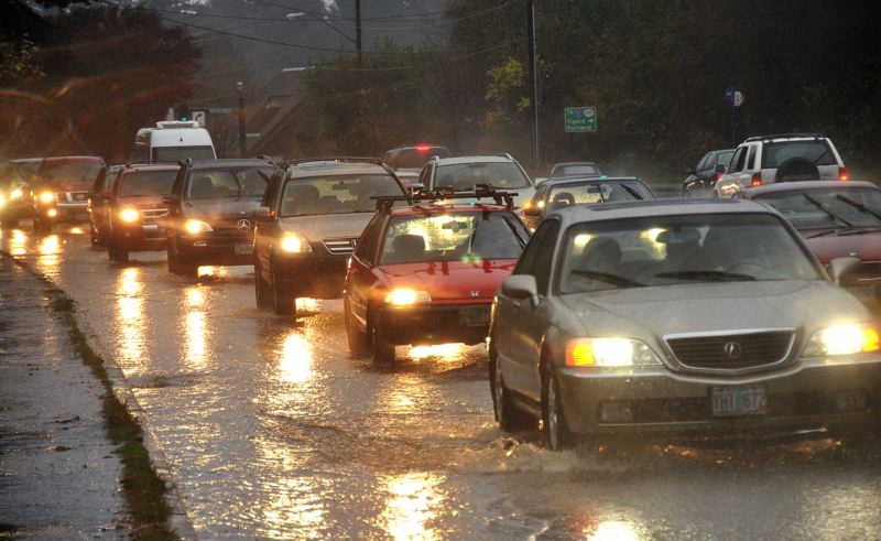 by: PAMPLIN MEDIA GROUP: VERN UYETAKE - High water slowed traffic on Southwest Boones Ferry Road in Lake Oswego Monday afternoon. Heavy rain flooded many local streets and forced TriMet to reroute some bus lines.