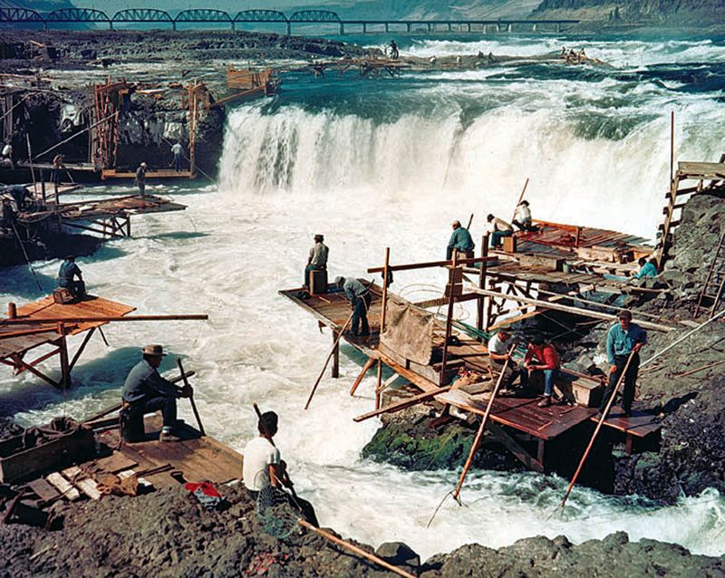 by: PHOTO COURTESY OF U.S. ARMY CORPS OF ENGINEERS  - Tribes fishing the waters of Celilo Falls in the 1950s, before construction of The Dalles Dam forced relocation of the oldest continuous  settlement of North America.