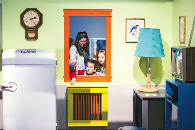 by: PAMPLIN MEDIA GROUP: CHRISTOPHER ONSTOTT - A family views an OMSI living area/kitchen that shows the many ways Americans waste energy in their homes.