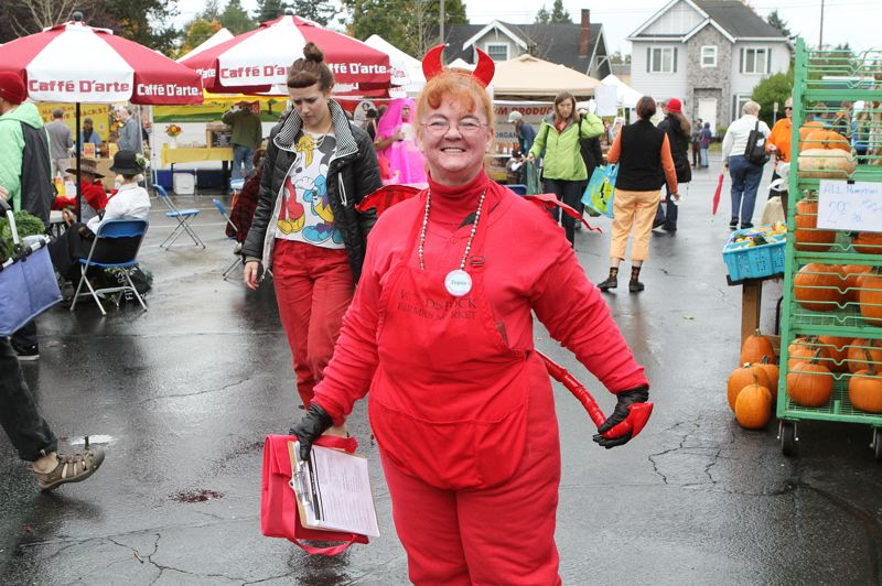 by: DAVID F. ASHTON - Dressed for the Halloween-themed final Woodstock Farmers Market, 'Lil Devil' Virginia Petersen welcomes those attending.