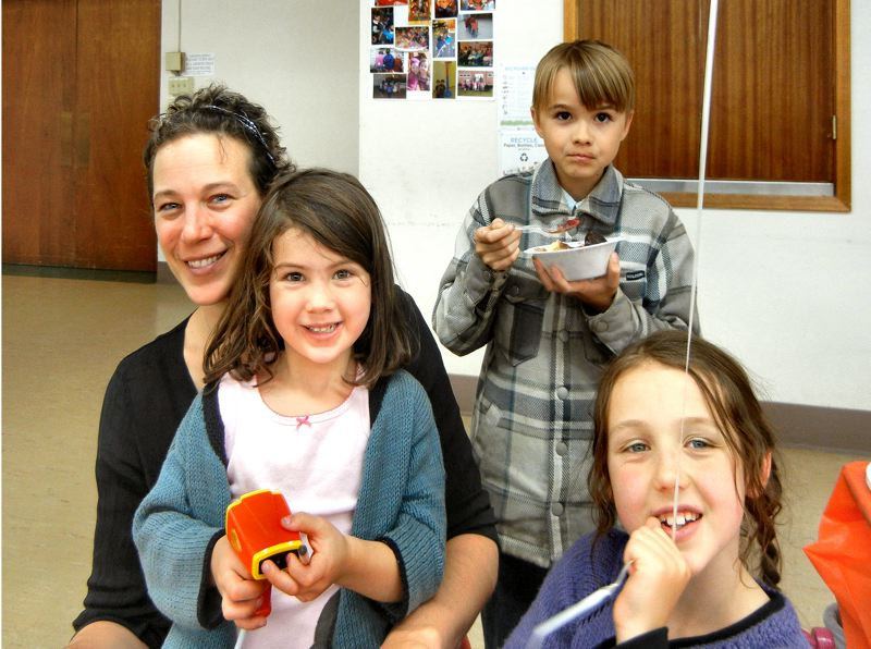 by: ELIZABETH USSHER GROFF - After helping to serve ice cream, Evan Hitchman, a fifth grader at Duniway Elementary, savors his own ice cream sundae at a fundraiser for Blooming Garden Preschool, where he attended until 2006. Blooming Garden's Teacher Pia and her two daughters, one a preschooler and one a graduate, enjoy the fun.
