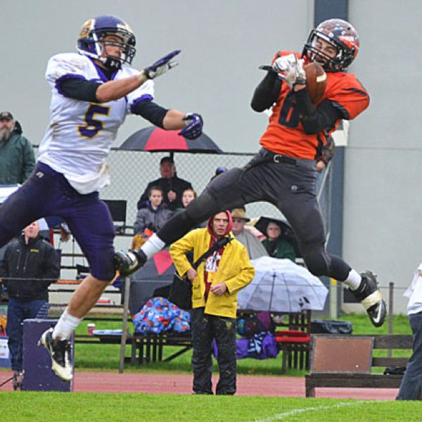 by: JOHN BREWINGTON - Scappoose's Paul Revis goes high for a pass during Saturday's game with Baker as Darren Dolby (5) tries to defend. This one slipped out of Revis' grasp and the Indians fell to Baker, 22-0.