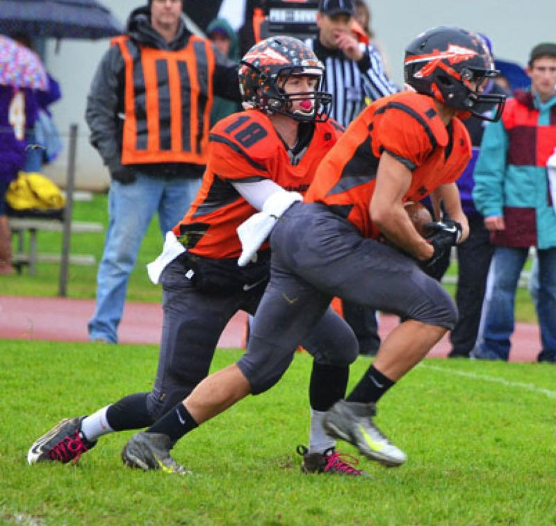 by: JOHN BREWINGTON - Quarterback Taylor Loss hands off to Carson Davison (1) during Saturday's game with Baker.